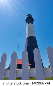 Tybee Island Lighthouse in Georgia against Blue Sky With Fence in the Foreground And Sun Flares