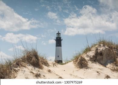 Tybee Island Lighthouse on the Atlantic Ocean in Georgia behind sand dunes.