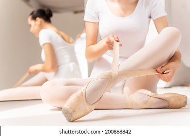 Tying her slippers before performance. Close-up of young ballerina in white tutu tying her slippers while sitting near the mirror