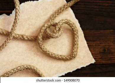 'Tying the knot' wedding invitation or save the date card.  Rope knotted into a heart shape with hand torn parchment paper on rustic wood background.  Macro with copy space.