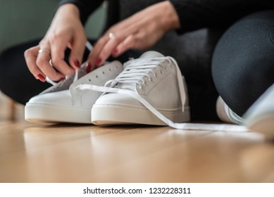 Tying white sneaker shoes