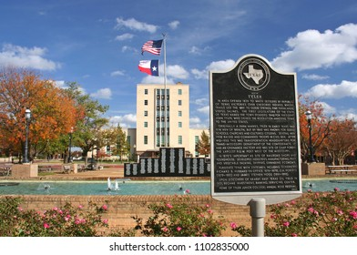 Tyler, Texas - November 14, 2011: Smith County Courthouse with historical marker and Tyler roses growing under historical marker. Texas flag and American flag flying over courthouse