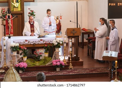 TYMOWA, POLAND - APRIL 26, 2020. Priest and altars boy at the altar during holy Mass in the Church Our Lady of Queen. Due to the pandemic Covid-19 coronavirus acolytes have face masks.
