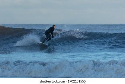 TYNEMOUTH, ENGLAND, UK, JANUARY 23, 2021.  Surfers on Longsands Beach, Tynemouth, North East England, UK. TYnemouth, England, UK, January 23, 2021.