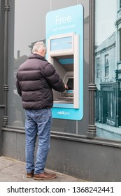 Tynemouth / Great Britain - April 06, 2019 : A man withdraws money from a Co-op Cash Point advertising Free Cash Withdrawls