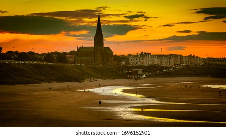 Tynemouth Longsands Beach with St Georges' Church in the background. Beautiful sunset, Orange Sky.