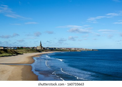 Tynemouth Longsands, looking towards St Georges Church Cullercoats, Tyne and Wear, UK.