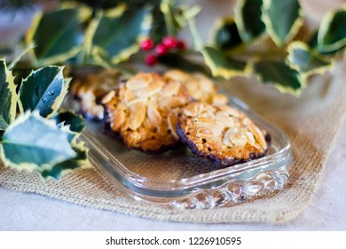 """Typcial traditional German almond and chocolate biscuits for the Christmas holidays called """"Florentiner"""" cookies on a decorated table top. Selective focus"""