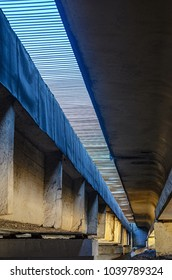 Type of concrete road bridge across the river view from below. Abstract industrial background with structural elements of an engineering structure