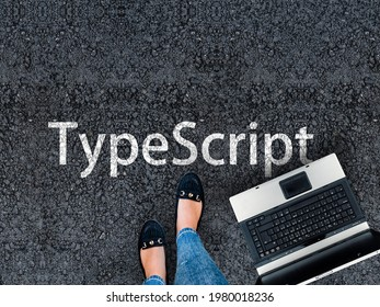 TypeScript Programming Language. Legs in sneakers standing next to laptop and word TypeScript