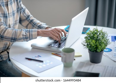 Typesetting. Hands of a man in a plaid shirt typing text on a white netbook, which is on a white table.