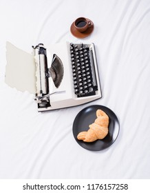 Typewriter and delicious croissant plate and coffee white bed sheets. Create inspiring atmosphere before start writing page typewriter. Benefit being writer is comfortable inspiring workplace.