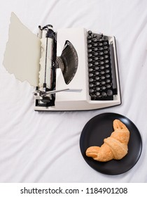 Typewriter and delicious croissant plate lay white bed sheets. Benefit being writer is comfortable inspiring workplace. Create inspiring atmosphere before start writing new page with typewriter.