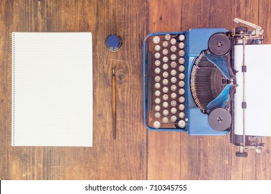 Typewriter with Empty Ark of Paper and Empty Notebook on Wooden Desk