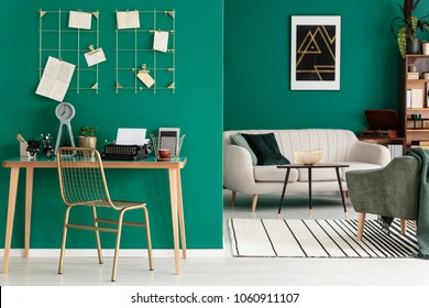 Typewriter and office supplies placed on a wooden desk standing in a green living room interior with couch and geometric poster on the wall