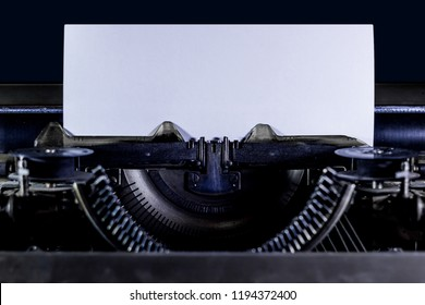 Typewriter on a black background with clear white page. Horizontal orintation