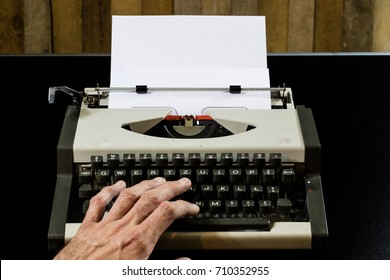 typewriter on the black table. White blank card. Wall of rough boards. black background