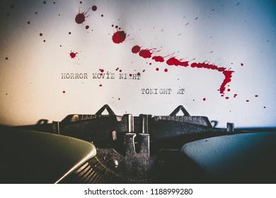 Typewriter spelling horror movie night on paper with blood splashes
