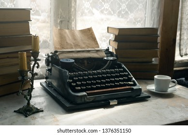 Typewriter, stack of books, candle and a cup of coffee or tea on a writer table background.