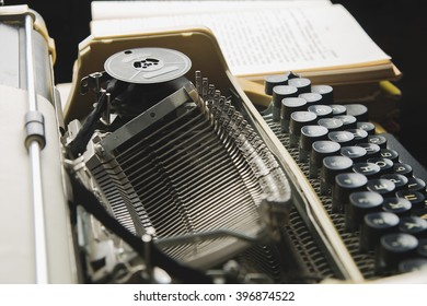 typewriter and a stack of books lying around
