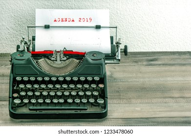 Typewriter with white paper page on wooden desk. Business concept. Sample text AGENDA 2019