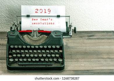 Typewriter with white paper page on wooden table. sample text 2019 New Year's Resolutions. vintage style toned picture