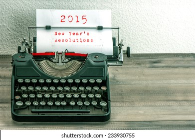 Typewriter with white paper page on wooden table. sample text 2015 New Year's Resolutions. vintage style toned picture