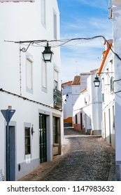 Typic street of medieval downtown os Évora, Portugal, with portuguese achtecture, white houses and brick streets in the Alentejo region that is known by your wine production and food.