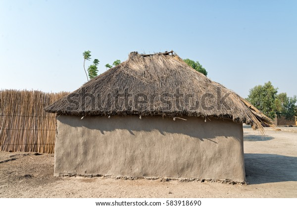 Typical African thatched roof hut of the Subiya people with walls made of mud and cow dung in a village on the Chobe river bank, Namibia