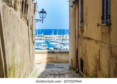 Typical alley in Otranto (Lecce); harbor view on background. Puglia, Italy
