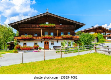 Typical alpine house decorated with flowers near Kirchberg village on sunny summer day, Tirol, Austria