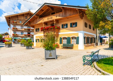 Typical alpine houses decorated with flowers on square of Kirchberg village on sunny summer day, Tirol, Austria