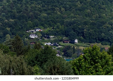 Typical alpine houses nestled on a hill amongst trees by Lake Annecy France