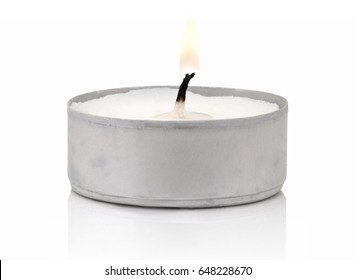 Typical aluminium burning tea candle isolated on white background with shadow reflection. Tea candle with flame and black wick. Tea candle with burning ingle and burned candlewick. Macro photography