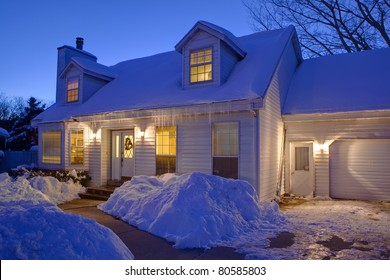 Typical American home with icy winter snow - evening twilight - cape cod style