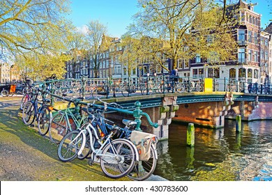 The typical Amsterdam street in sunny spring evening. Bicycles parked on a bridge in the channel, Netherlands.