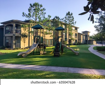 A typical apartment complex building with a central playground swing, stairs in suburban area at Humble, Texas, US. View from grassy backyard, surrounded by green trees in early morning with blue sky.