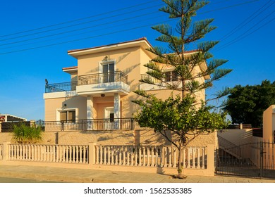 Typical architecture in suburbs, Cyprus. Garden fence behind sunny summer day. Modern luxury cottages and apartments. beautiful city landscape in background of blue sky. duplex house. new Townhouses