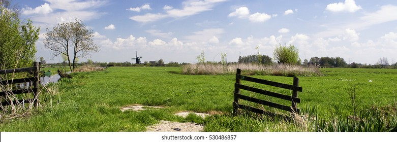 Typical attractive dutch landscape with windmill, green grass, wooden fence, blue sky, white clouds and trees