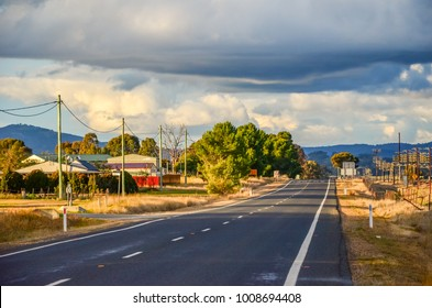 Typical Australian country highway with utility poles erected along the road. Landscape of regional Australia with rural houses, trees in village and mountains in distance. Illabo, New South Wales.