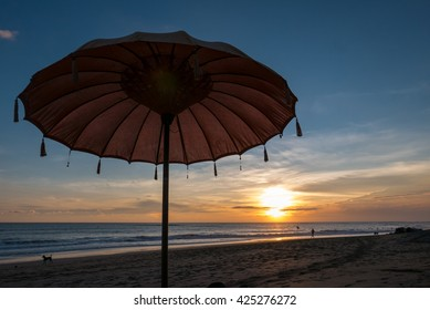 Typical Balinese sun umbrella standing on the beach during sunset in Chenggu beach on Bali Island with silhouettes of people in the background. Indonesia