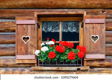 Typical bavarian or austrian wooden window with red geranium flowers on house in Austria or Germany