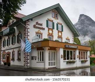 Typical Bavarian hotel in the village famous for it's Passion Play held every 10 years, with iconic Kofel Mountain Peak in background.  Oberammergau, Germany. Aug 2019