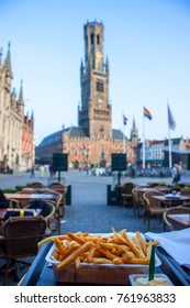 Typical belgian meal - fries, Bell Tower and Market Square in Bruges in background. Shallow DOF.