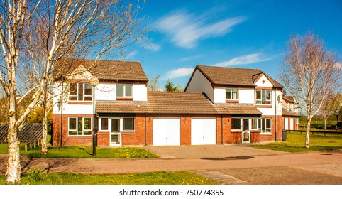 A typical British house, semi detatched with a garage and grass garden out front.