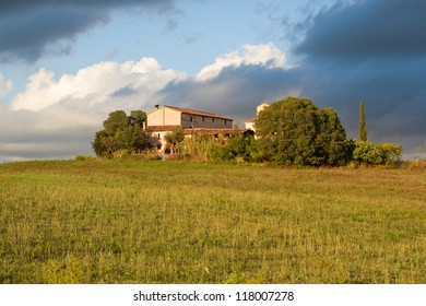 Typical Catalan farmhouse with storm on the background taking over the farm