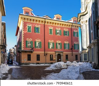 Typical colorful building on narrow cobblestone street with snow in city of Cuneo in Piedmont, Northern Italy.