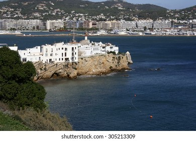 Typical constructions of white houses in the town of Ibiza, Watch tower at the entrance to the port of Ibiza, Hotels along the beach, places to stay, Ocean waves crash on shore, white houses,