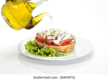 typical Cretan plate called ntakos, a slice of barley bread , cubes of tmato, goat cheese, virgin olive oil and herbs