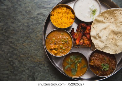 Typical curry set meal of meals south India with Chicken Tandoori, Mutton Curry, Subji (Vegetarian Curry),Papadum,Nan,Raita (Yogurt with cucumber),Mutter Paneer ,and Pulao Rice